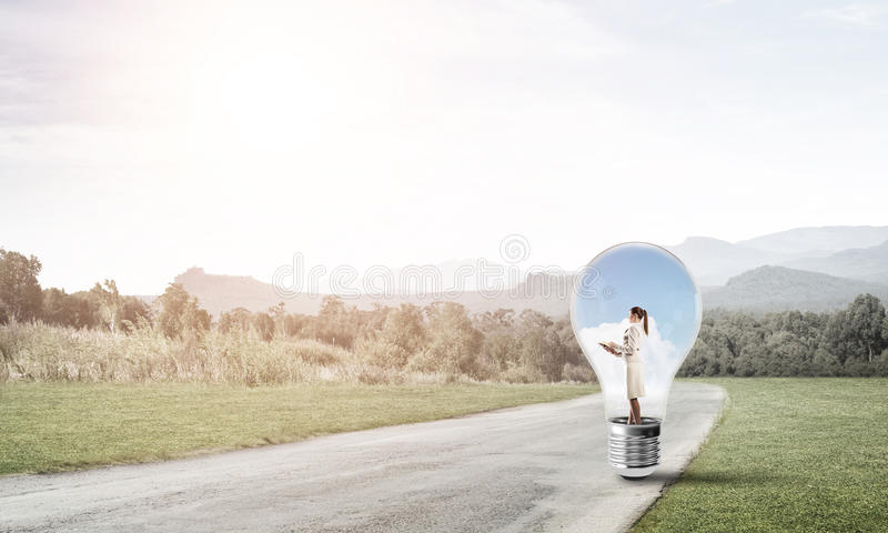 Businesswoman inside light bulb. Young businesswoman trapped inside of light bulb on countryside road stock photo