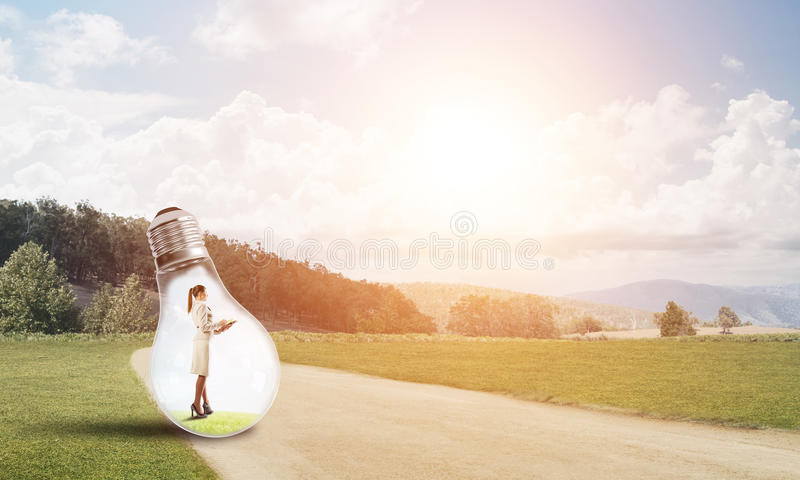 Businesswoman inside light bulb. Young businesswoman trapped inside of light bulb on countryside road stock images