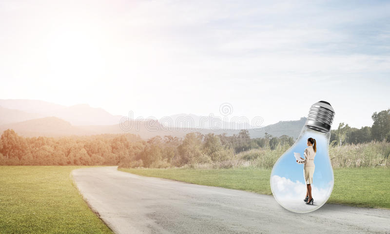 Businesswoman inside light bulb. Young businesswoman trapped inside of light bulb on countryside road stock image