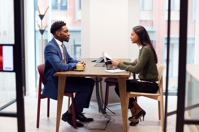 Businesswoman Interviewing Male Job Candidate In Meeting Room stock images