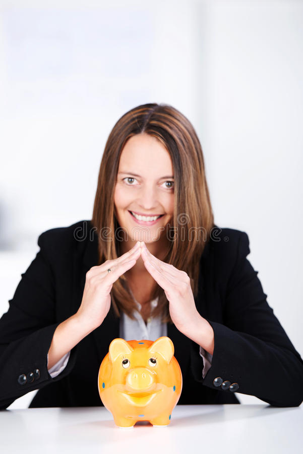 Download Businesswoman Joining Fingers Above Piggybank At Desk Stock Photo - Image: 31474302