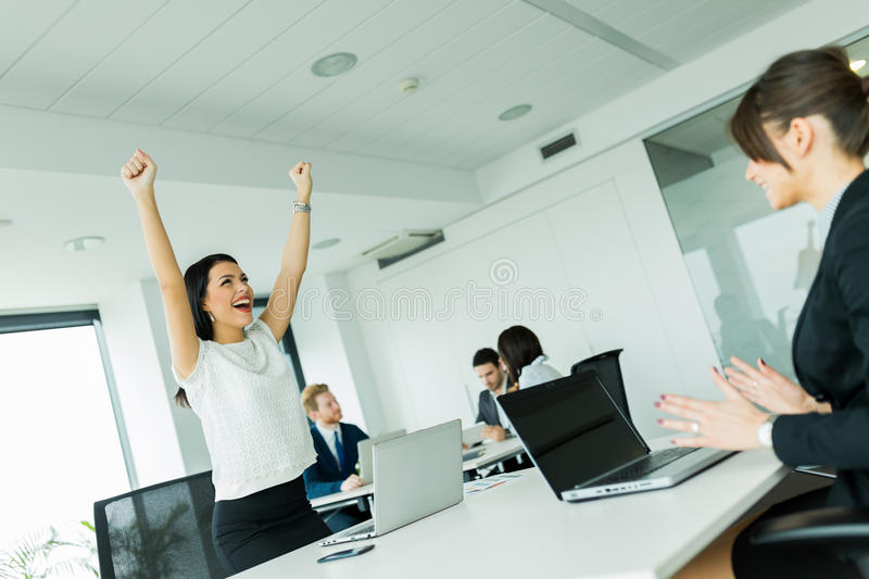 Businesswoman jumping from joy and raises hands as a sign of suc stock images
