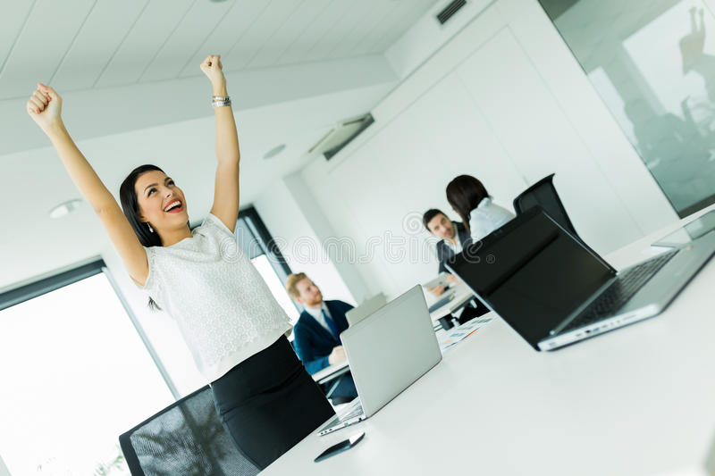 Businesswoman jumping from joy and raises hands as a sign of suc stock photography