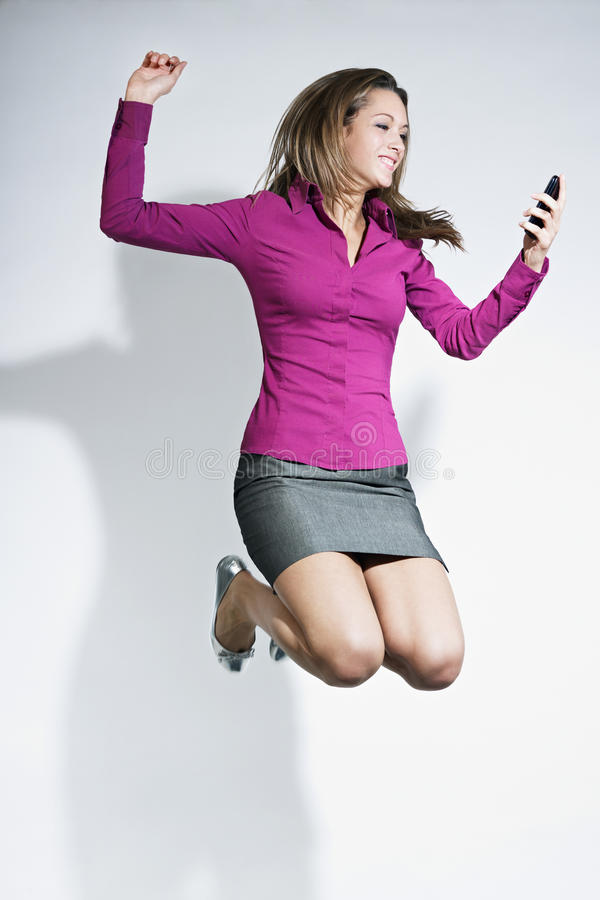 Businesswoman Jumping With Mobile Phone In Hands Royalty Free Stock Image