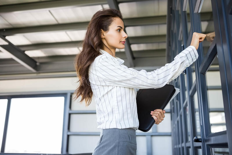 Businesswoman knocking on door. In office royalty free stock photo