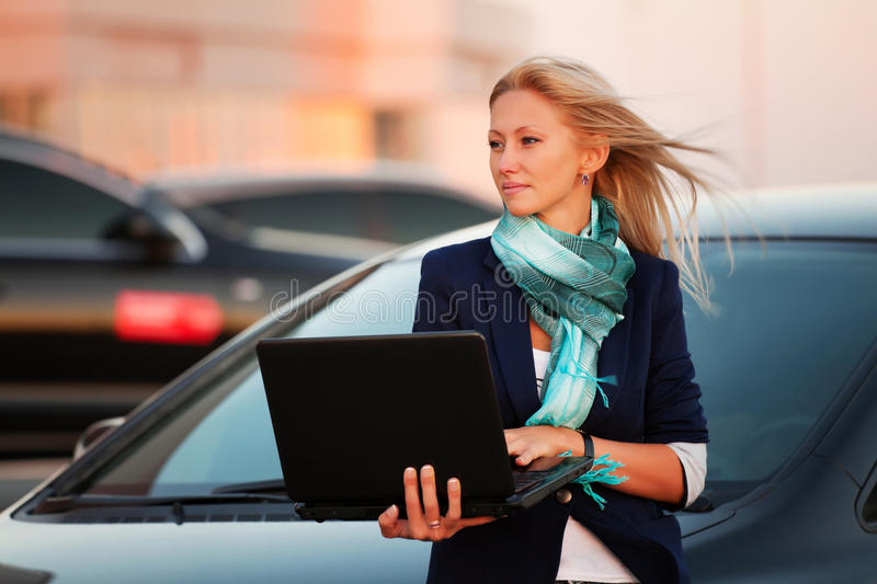 Young fashion business woman with laptop leaning on her car royalty free stock photo