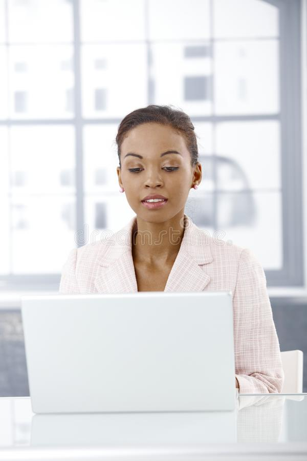 Businesswoman with laptop. Businesswoman sitting in office using laptop computer, looking at screen royalty free stock images