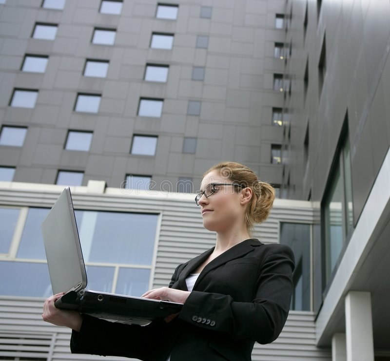 Businesswoman with laptop computer on the city stock photos