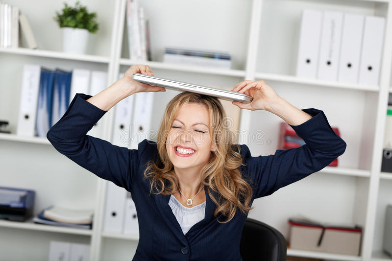 Download Businesswoman With Laptop On Head Clenching Teeth Stock Photo - Image: 31228434