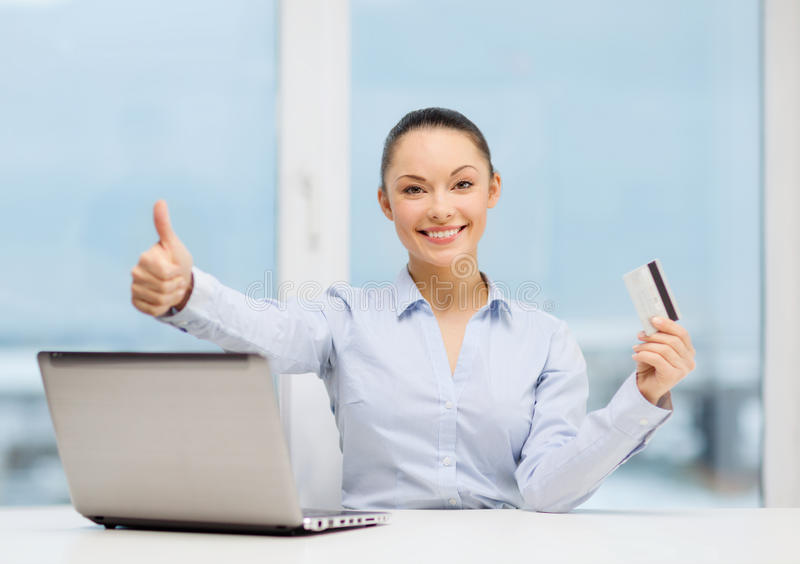 Businesswoman with laptop in office. Business, investing and technology concept - businesswoman with laptop and credit card in office showing thumbs up stock images