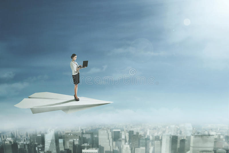 Businesswoman with laptop on paper plane. Young businesswoman using a laptop computer while standing on a big paper plane while flying on above a city stock photography