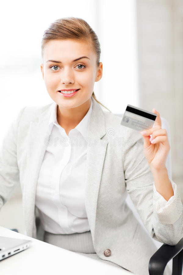 Businesswoman with laptop showing credit card. Smiling businesswoman with laptop showing credit card stock photography