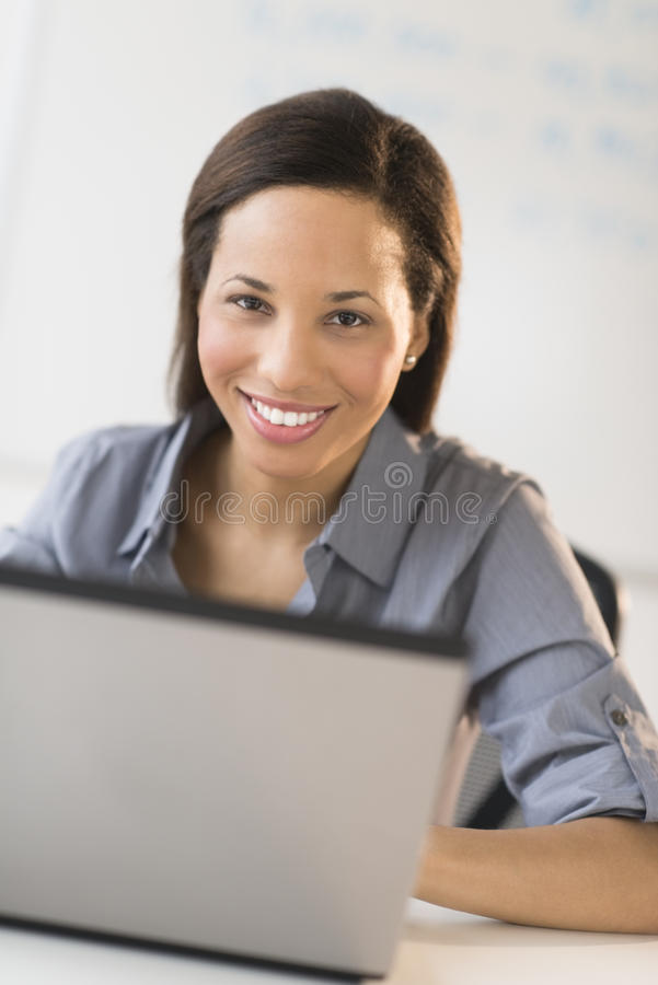 Download Businesswoman With Laptop Sitting At Desk In Office Stock Photo - Image: 32429714