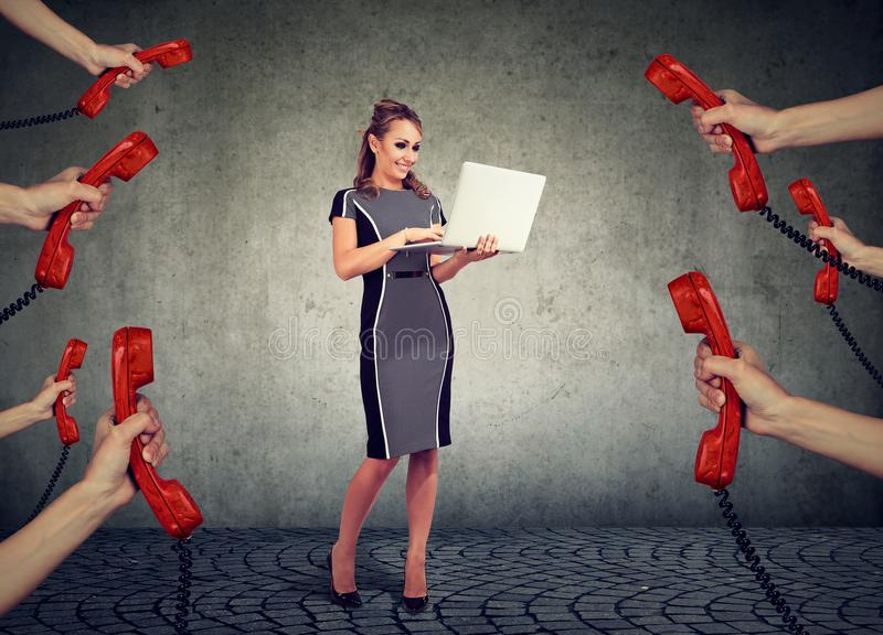Beautiful businesswoman with laptop surrounded by many hands with phone headsets stock photo
