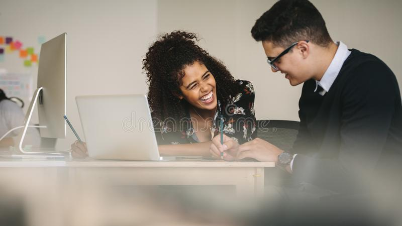 Businesswoman laughing during a discussion with colleague at wor stock photo