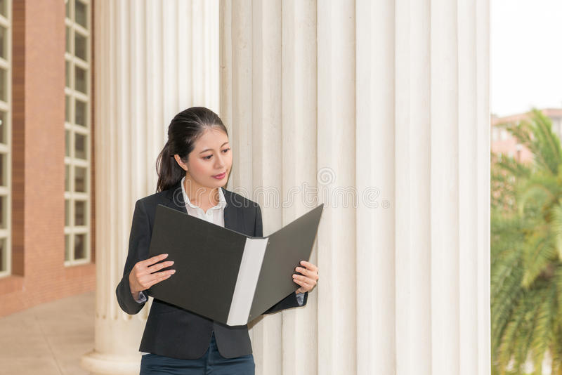 Businesswoman lawyer holding folder and reading. Legal case information about litigation content standing in court building waiting for customers royalty free stock photo
