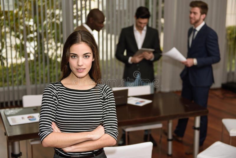 Businesswoman leader with arms crossed in working environment. Young businesswoman leader looking at camera with arms crossed in working environment. Group of royalty free stock photos