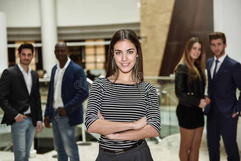 Businesswoman leader looking at camera in working environment. Young businesswoman leader looking at camera in office building. Group of multi-ethnic people in stock photography