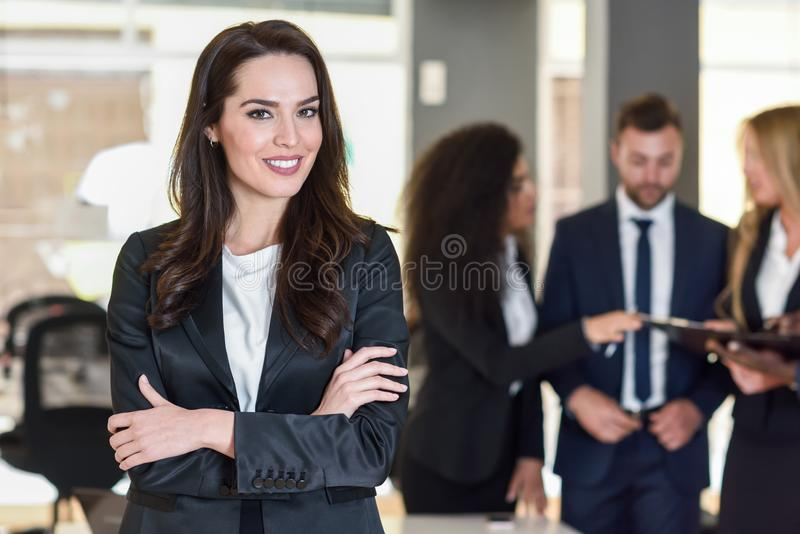 Businesswoman leader in modern office with businesspeople working at background stock photos