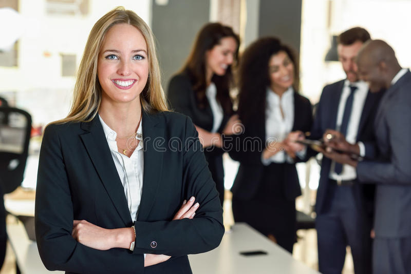Businesswoman leader in modern office with businesspeople working at background stock photography