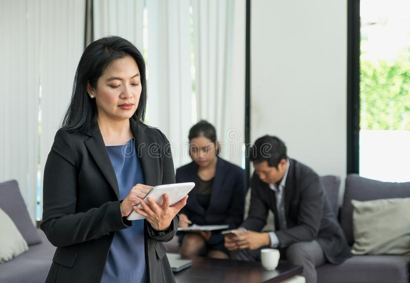 Businesswoman leader using tablet with team in corporate meeting. At office,Female leadership concept stock images