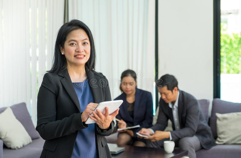 Businesswoman leader using tablet with team in corporate meeting. At office,Female leadership concept royalty free stock photos