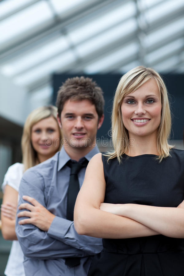Businesswoman leading her team with folded arms. Beautiful blonde businesswoman leading her team with folded arms royalty free stock image