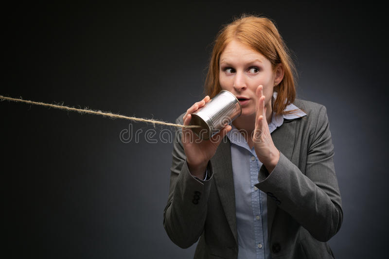Businesswoman Leaking Corporate Secrets. Young businesswoman tells a secret or shares confidential information through a can and a string phone royalty free stock photography
