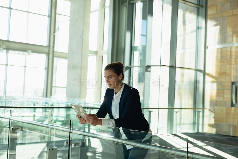 Businesswoman leaning on railing and using digital tablet in a modern office building. Front view of businesswoman leaning on railing and using digital tablet in royalty free stock image