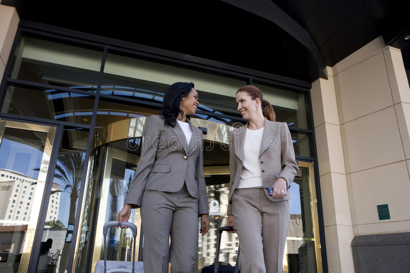 Businesswoman leaving hotel with luggage royalty free stock image