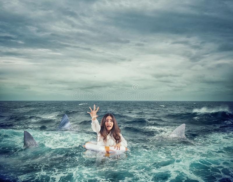 Businesswoman with lifebelt surrounded by sharks asks help stock photo