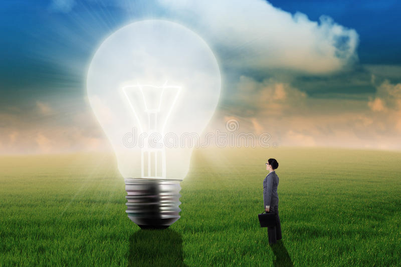 Businesswoman Looking At Big Light Bulb stock photography