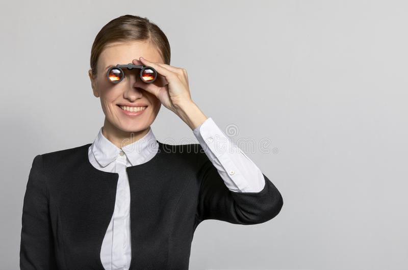 Businesswoman looking through binoculars. To the side and smiles.. The concept of the business and finding success. Model in a suit on a light gray background stock image