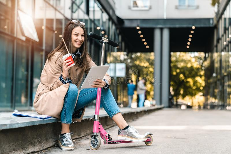 Businesswoman looking at the camera while holding a tablet next to a scooter stock photos