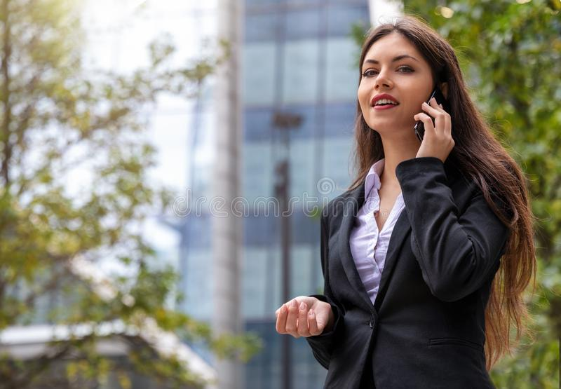 Businesswoman looking into camera outdoors in the city. Young, attractive businesswoman talking on mobile phone and looking into camera outdoors in the city royalty free stock photo