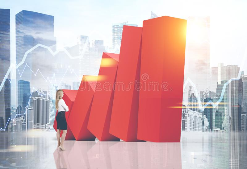 Businesswoman looking at falling graph in city stock image
