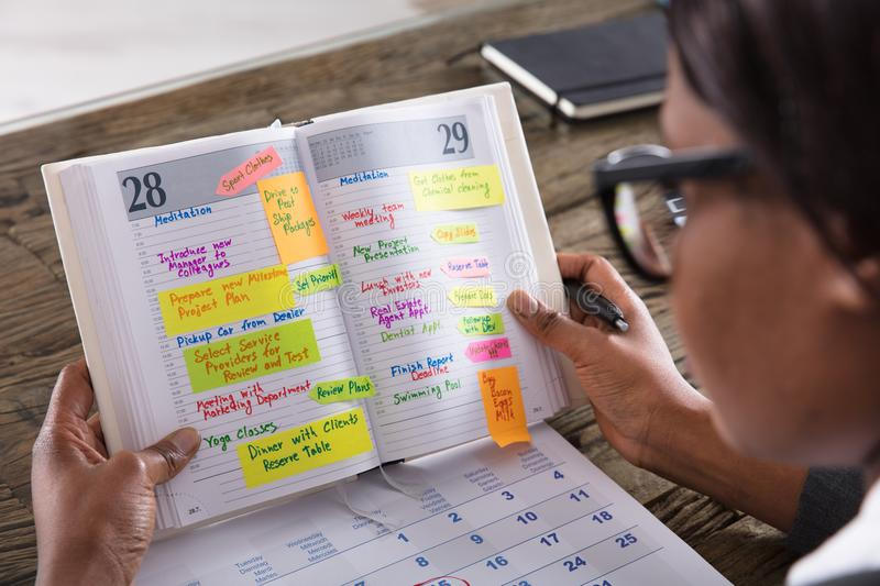 Businesswoman Looking At List Of Business Work In Diary. With Calendar On Desk stock photo