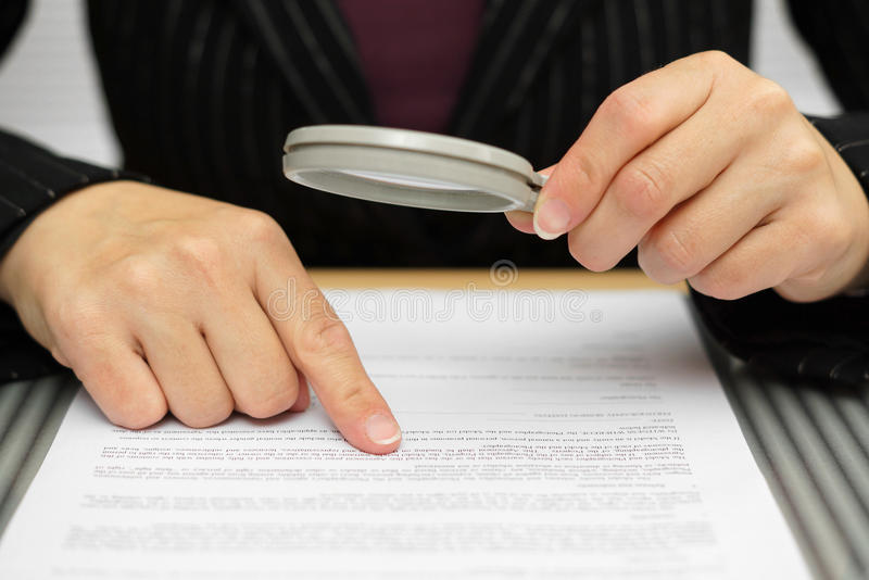 Businesswoman looking through a magnifying glass stock photo