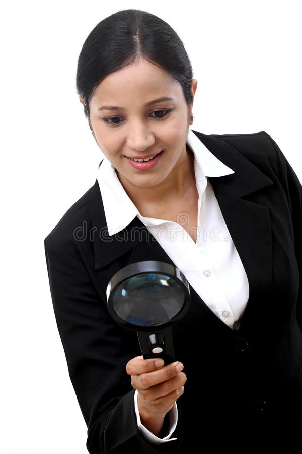 Businesswoman looking through a magnifying glass stock photography