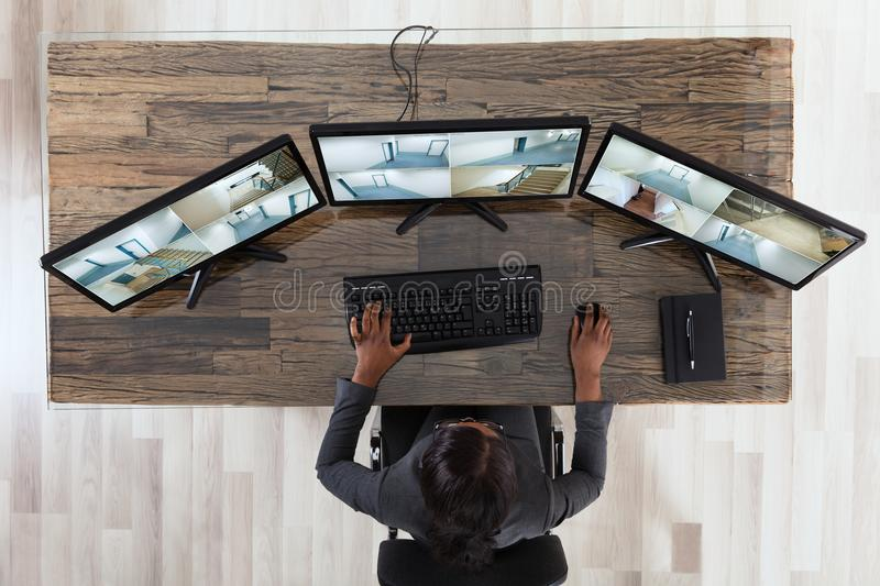 Businesswoman Looking At Multiple Camera Footage In Office. High Angle View Of A Businesswoman Looking At Multiple Camera Footage In Office stock photo