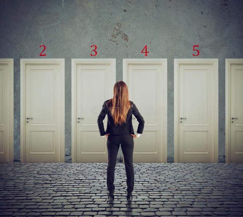 Businesswoman looking to select the right door. Concept of confusion and competition royalty free stock photo