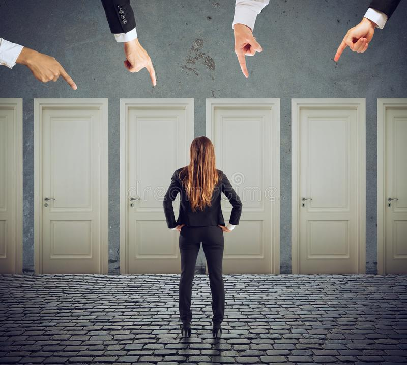 Businesswoman looking to select the right door. Concept of confusion and competition royalty free stock image