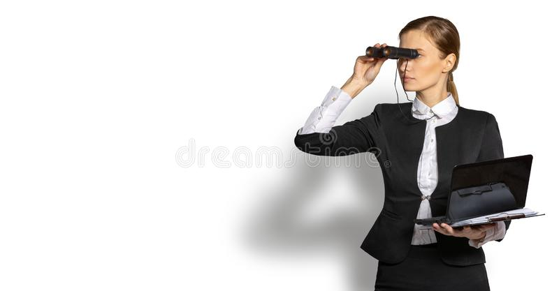 Businesswoman looks through binoculars. Businesswoman with a laptop in his hand looking through binoculars in the hope of prospects and success. The concept of royalty free stock image