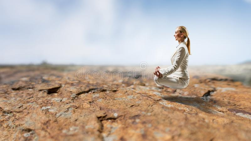 Businesswoman in lotus pose. Mixed media stock image