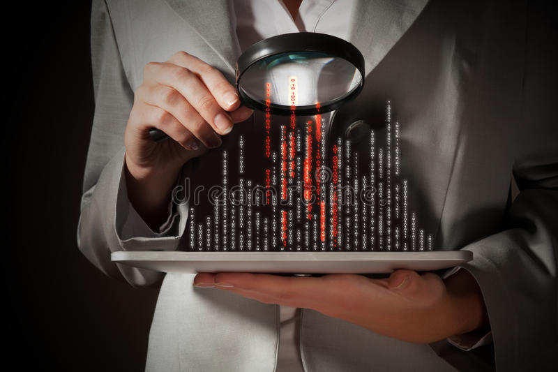 Businesswoman with magnifier glass. Examining binary code royalty free stock images