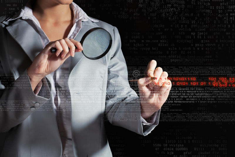 Businesswoman with magnifier glass. Examining binary code stock images