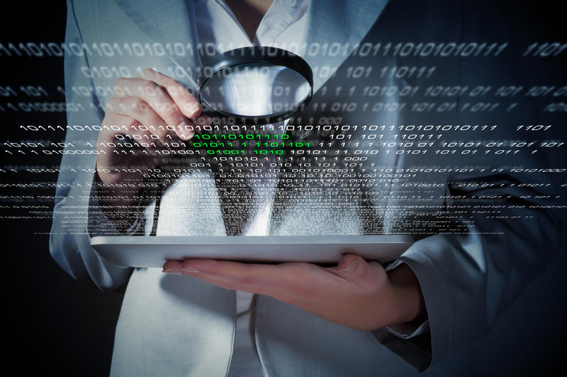 Businesswoman with magnifier glass. Examining binary code royalty free stock image