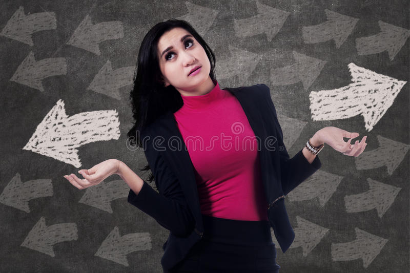 Businesswoman making a choice. With two arrow sign royalty free stock photo