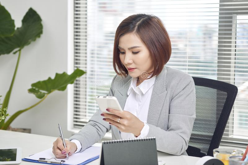 Businesswoman making notes looking at a cellphone at office. Woman entrepreneur sitting at the table writing notes while working royalty free stock images