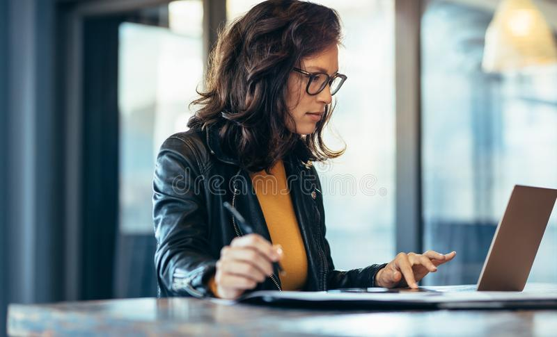 Businesswoman making notes looking at a laptop stock photography